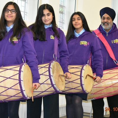 3 girls and their dhol teacher getting ready to play dhol drums