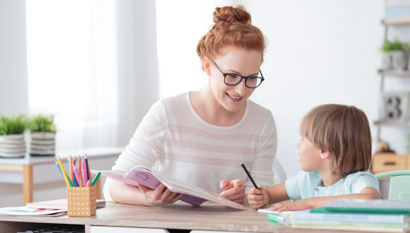 Teacher helping student with their work, both are smiling
