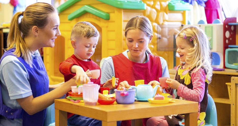 Children playing with teachers and with a toy cooking set