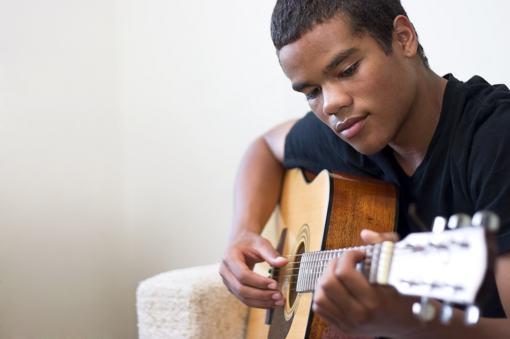 Teenage boy playing guitar at home