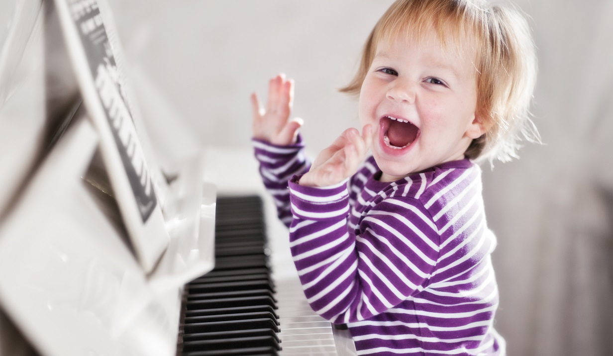 girl smiling and playing piano