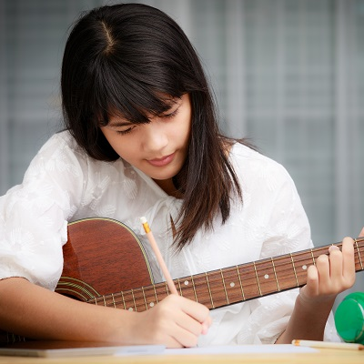 girl holding a guitar and writing notes