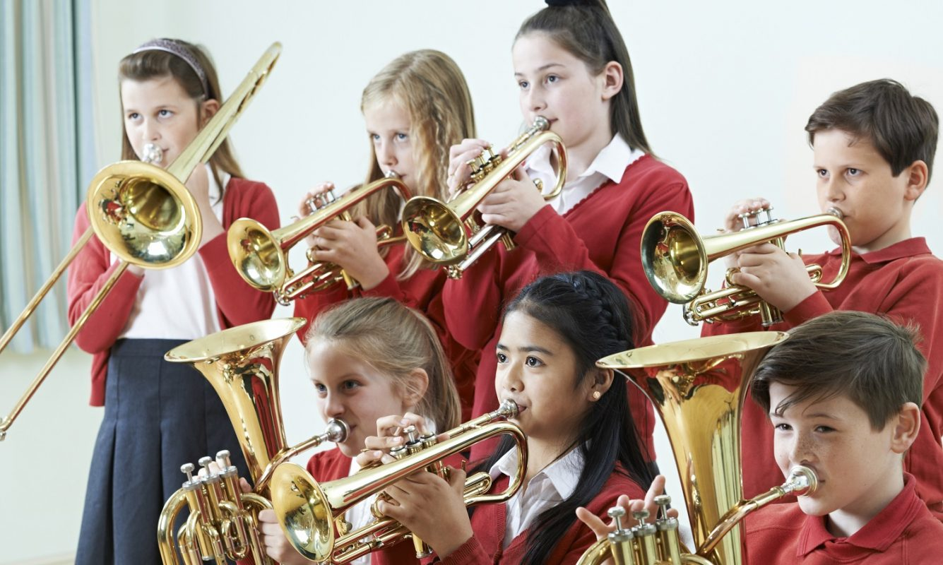 Group of children playing instruments in class in school uniform