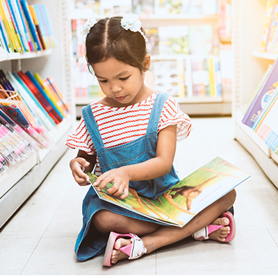 Little girl sat in a library on the floor reading a book