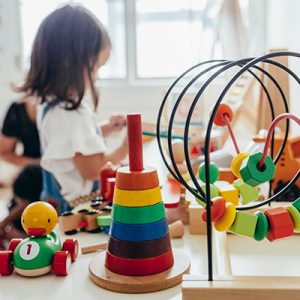 Picture of a little girl playing with colourful wooden educational toys