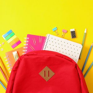 Picture of a red back pack on a yellow background with stationary coming out of it