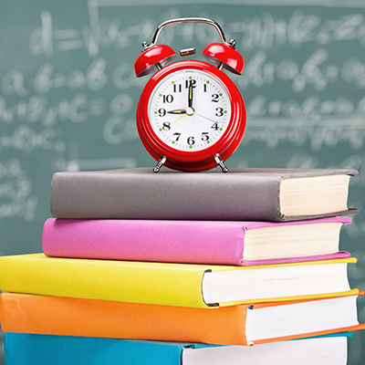 Stack of colourful books with an alarm clock on top and blackboard background