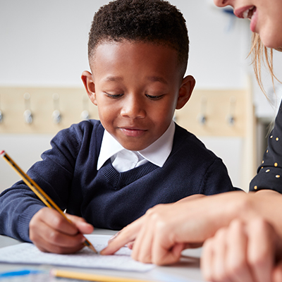 Little boy writing in his workbook at school with teacher